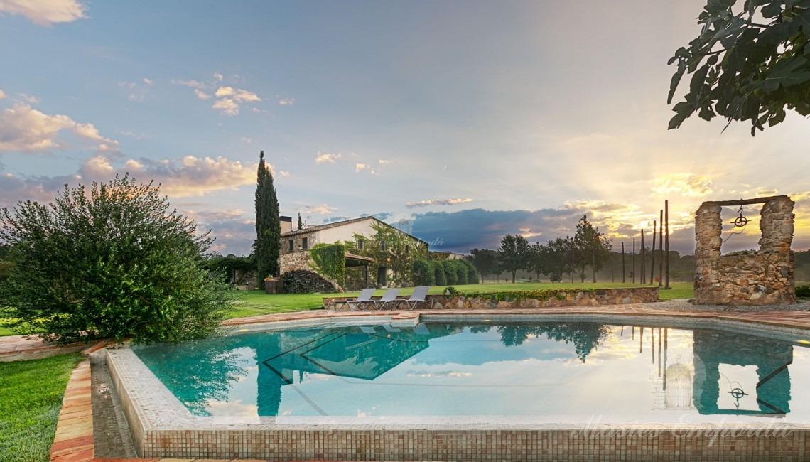 Vistes de la piscina i la masia al fons de la imagen