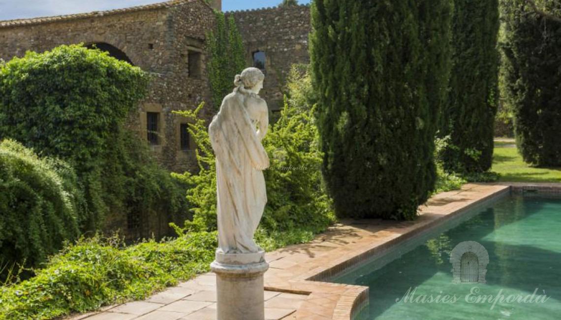Vista de la piscina rodeada de cipreses con una preciosa estatua estilo romano y como fondo la masía