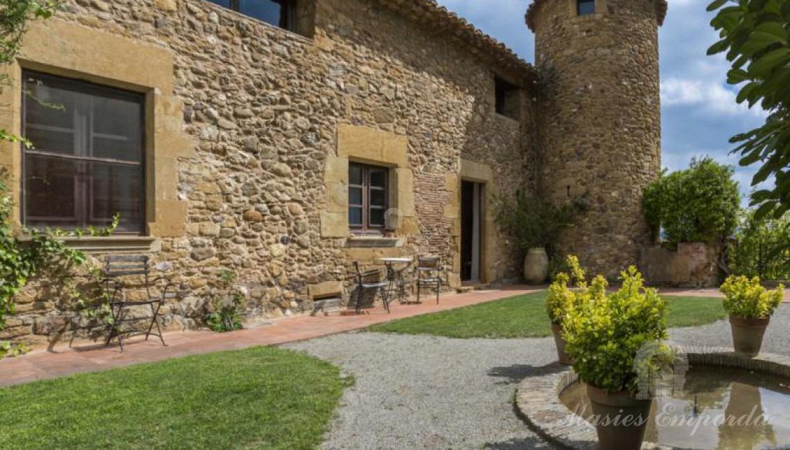 Vista del interior del patio superior de la casa con entrada lateral a la masía con torre circular de defensa y jardín con pequeño estanque.