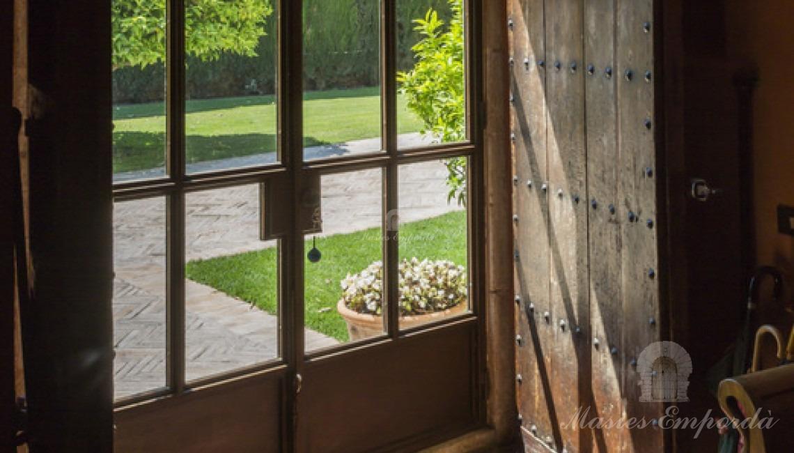 Detalle del hall de entrada desde la parte interior donde se aprecia la puerta exterior de forja y acristalada y la contra puerta de madera y herrajes en forja.