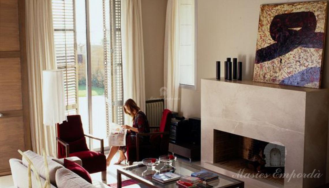Detalle del salón con chimenea de la casa con vistas a la piscina