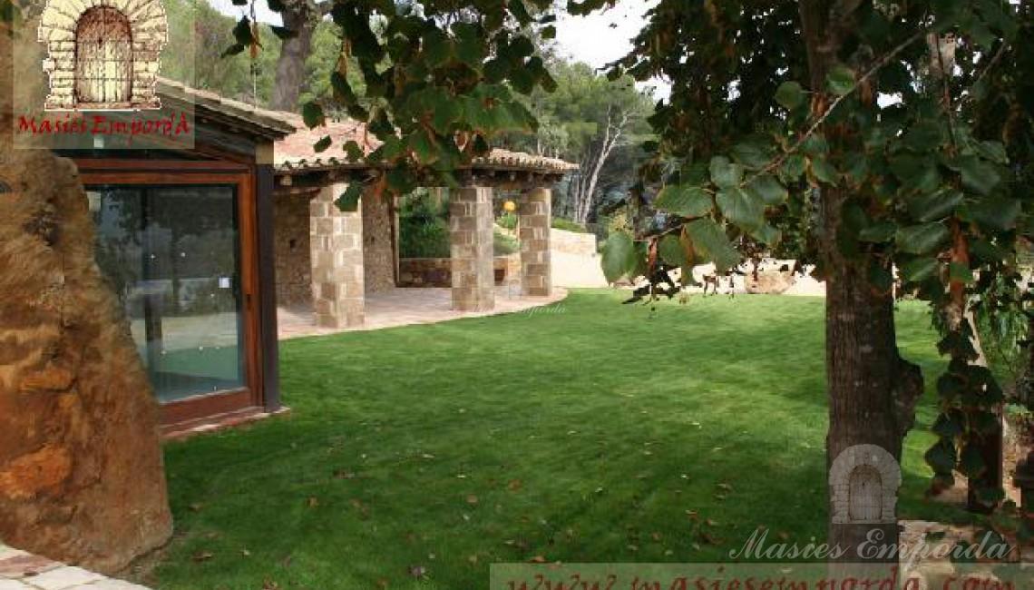 Detalle del porche exterior ubicada en la  fachada lateral de la masía con parte del jardín