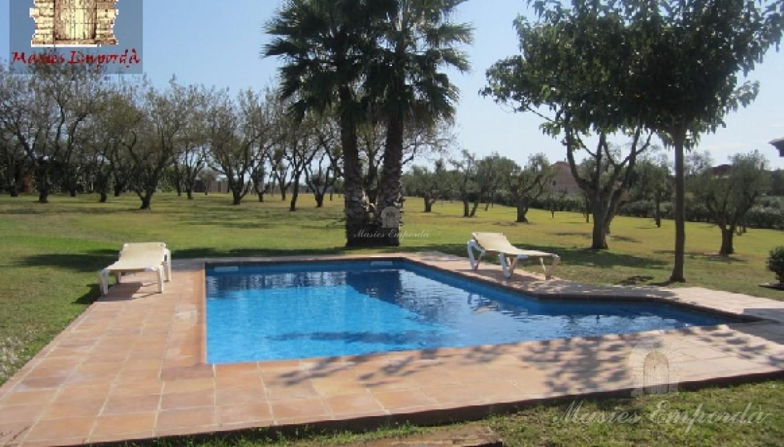 Vista de la piscina y solárium con el jardín al fondo de la imagen