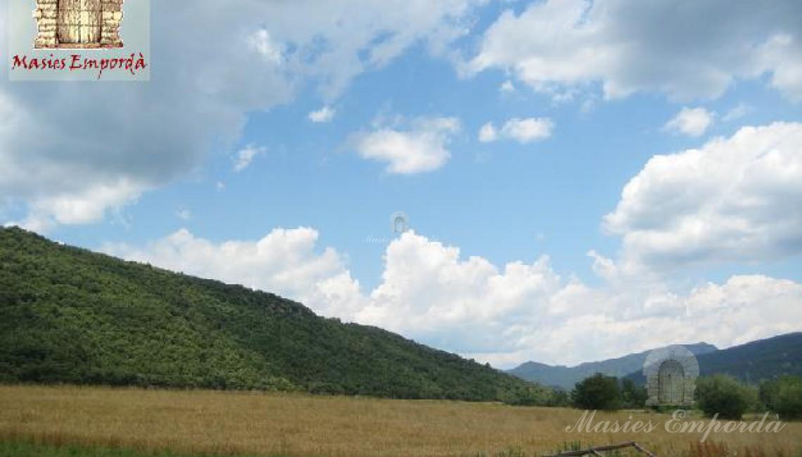 Vista de los campos que rodean la propiedad y colinas colindantes como fondo el azul del cielo moteados de nubes blancas