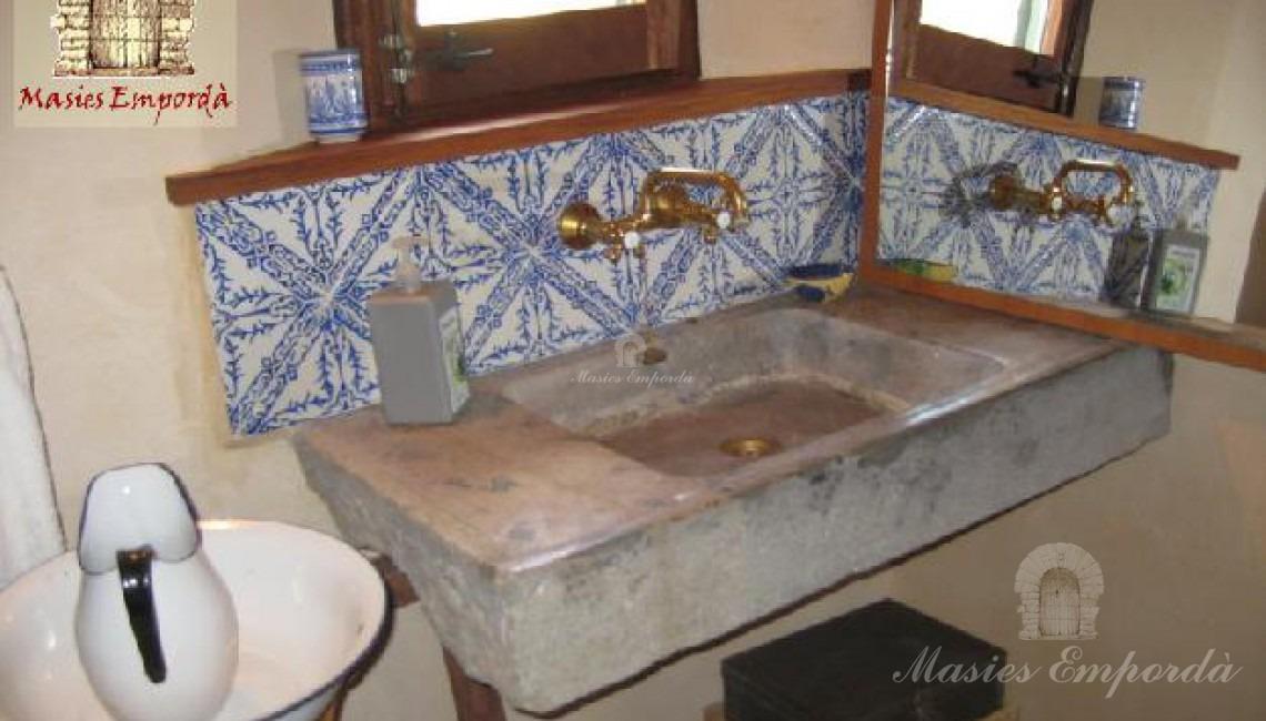Baño de planta con pica de piedra y azulejos de cenefas azules en fondo blanco