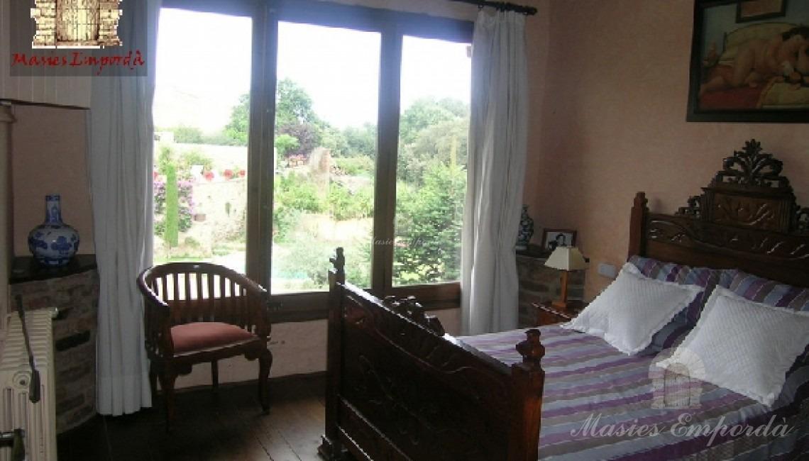 Segunda suite de la segunda planta con gran ventanal con vistas y techo con vigas de madera vistas