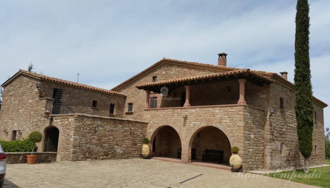 Vistas lateral de la fachada de piedra y entrada a la Masía donde se aprecias los diferentes cuerpos porche cubierto y arcos de piedra que le dar un aspecto castellesco.