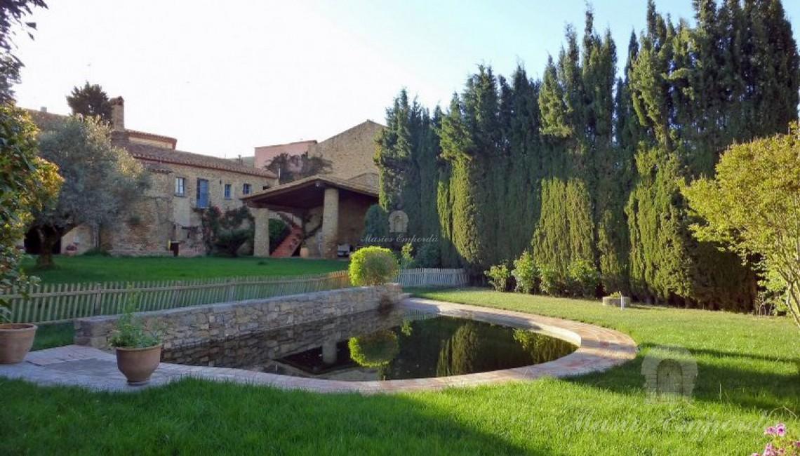Vista de la propiedad con la piscina en primer plano y la masía en segundo junto al porche anexo a la casa como comedor y barbacoa de verano