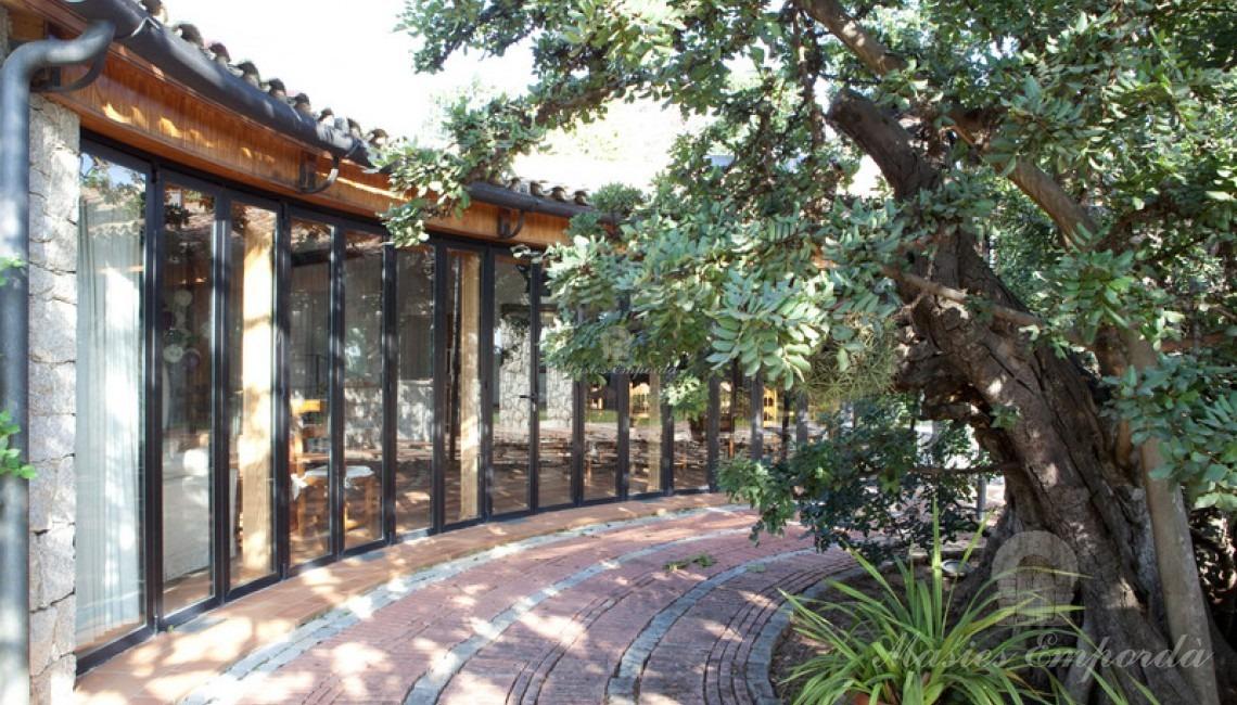 Vista lateral de la entrada a la casa de invitados de la propiedad y salón comedor barbacoa