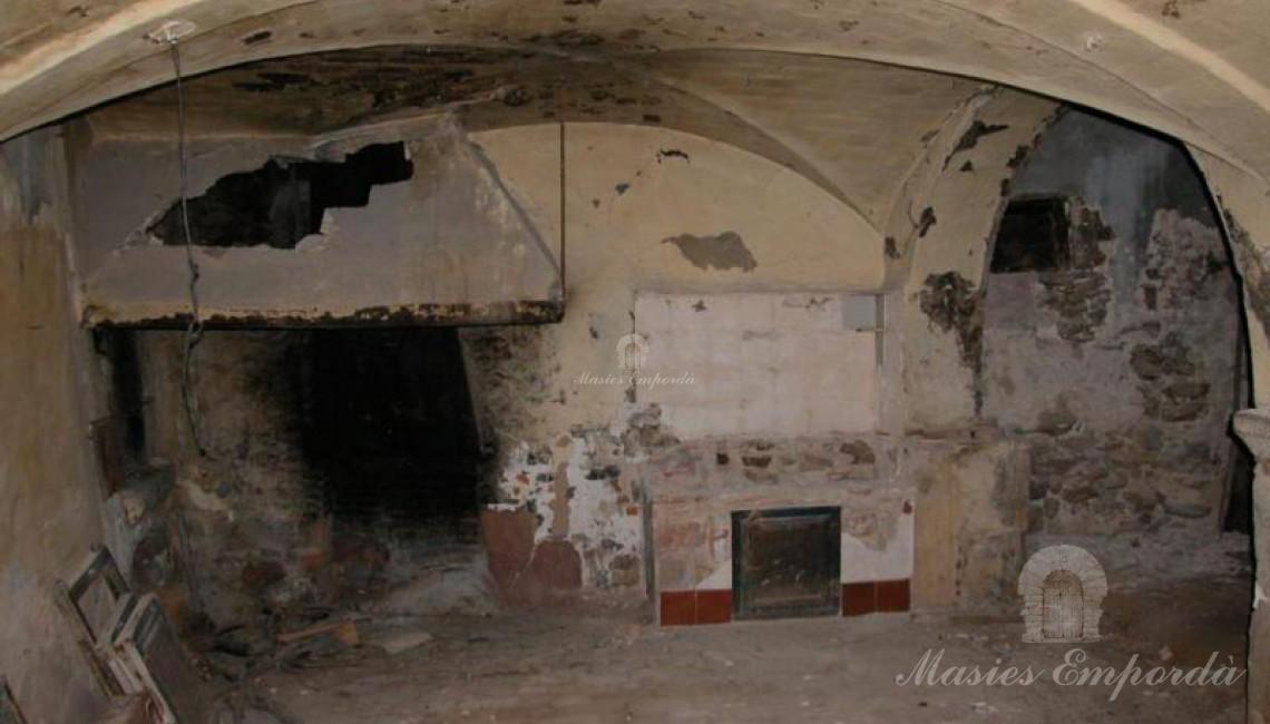 Vista de la cocina con la chimenea abierta al fondo de la imagen