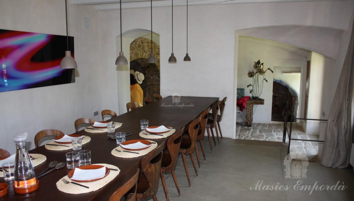 Vista desde el ángulo opuesto al pabellón del  comedor principal de la casa con mesa de hierro corten y el hall de entrada al fondo de la imagen