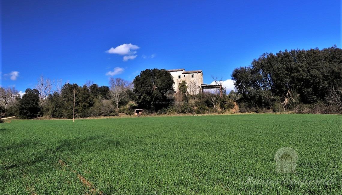 Vista de la masia des dels camps al costat del riu