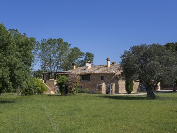 Vista lateral del conjunto constructivo de la masía rodeada del jardín de la propiedad