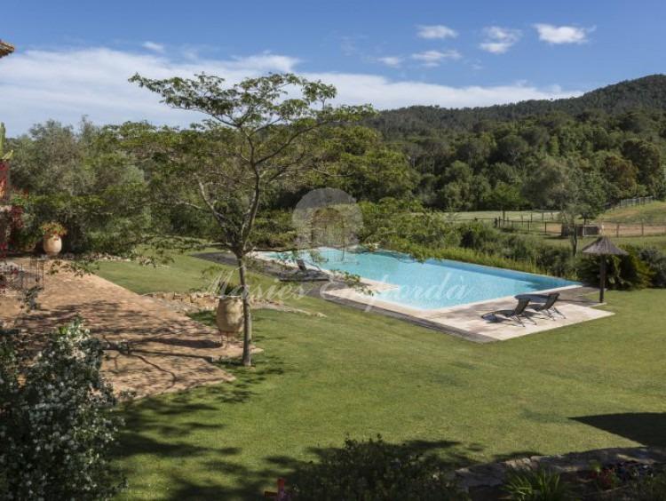 Vista de la piscina el jardín y parte de las montañas que rodean la propiedad