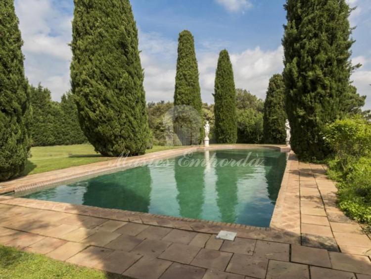 Vista de la piscina de la masía rodeada de cipreses