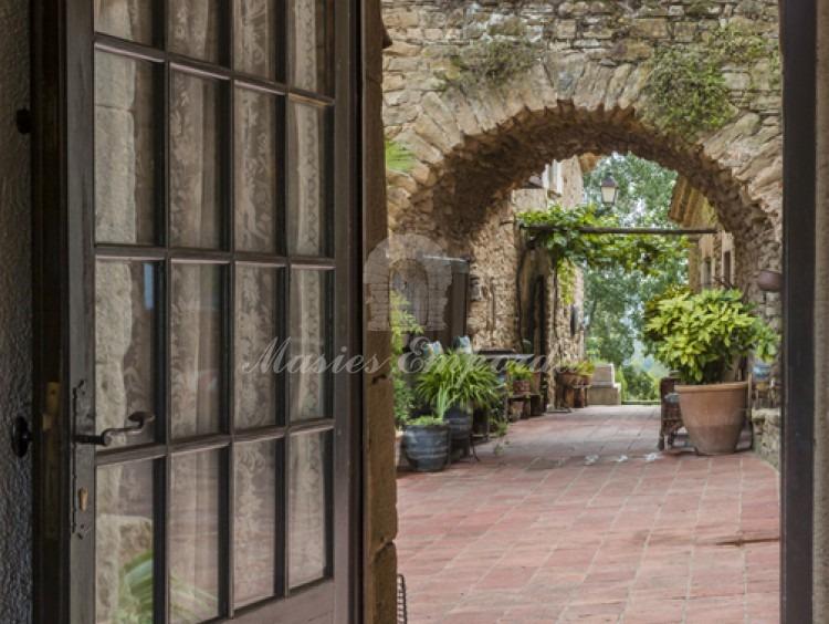 Vistes des de l'interior d'una de les cases que componen el conjunt amb vistes a l'arc de mig punt que conforma el pont de comunicació entre plantes de la masia principal i un annex.