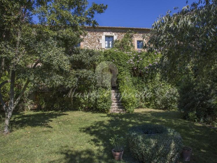 Façana principal del mas emboscada pel exuberant jardí que envolta la propietat amb escala d'accés a elles des del jardí i safareig.