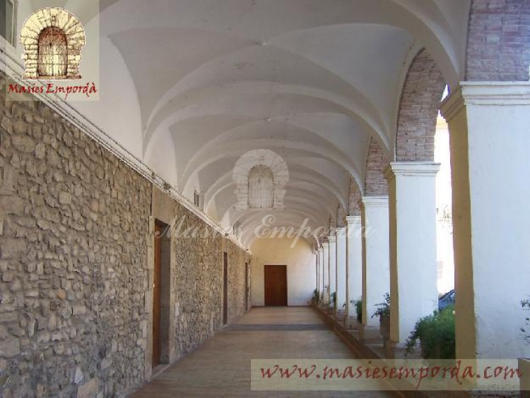 Vista del porche corrido en fachada con arcado de medio punto sobre pilares de piedra revocada y con bóvedas de crucería