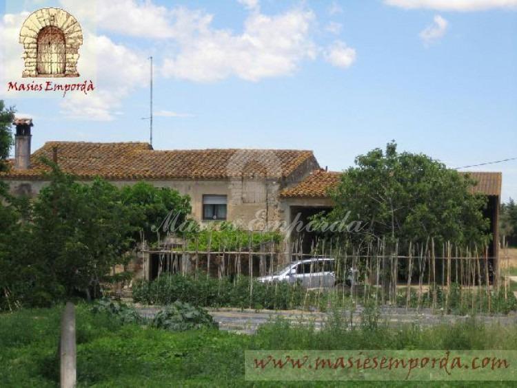 Fachada de la masía con emparrado, huerto y árboles frutales