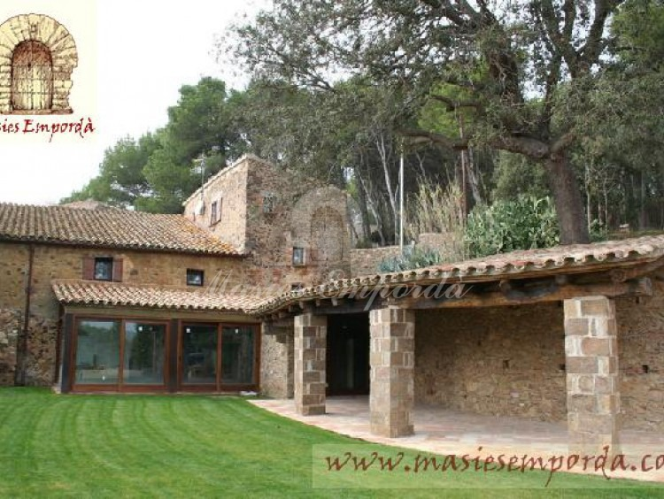 Vista del porche exterior y fachada lateral de la masía con parte del jardín