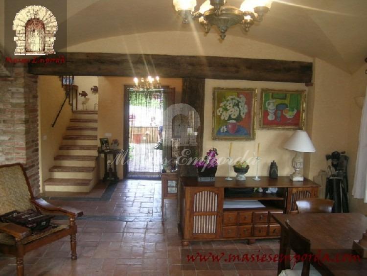 Detalle del salón comedor principal de la casa a dos niveles de altura y de pavimento con chimenea y vistas el jardín, piscina