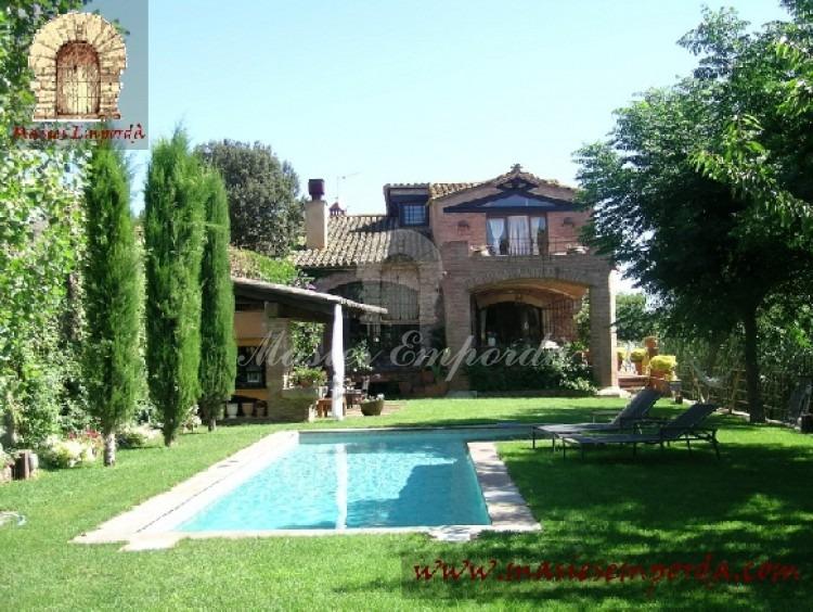 Vista de la piscina en primer término y de la casa al fondo de la imagen en el jardín de la propiedad.Situada a pocos kilómetros de las playas de Llafranch, Calella y Pals