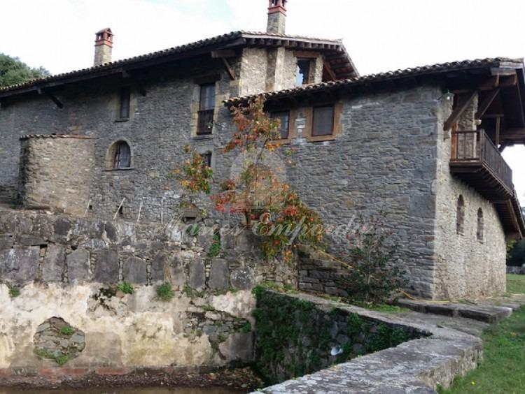 Lateral de la casa con detalle del balconera y cubierta voladiza con la balsa construida en piedra