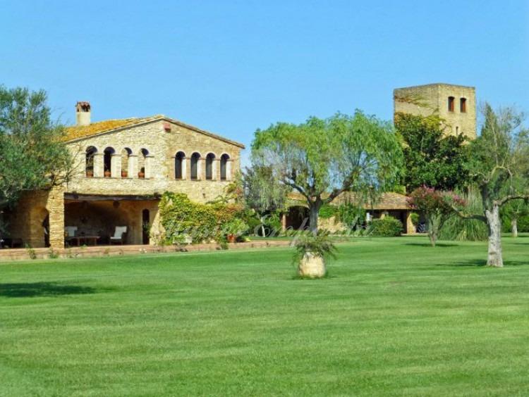 Vista lateral de la masía, los porches anexos y de la torre a ella con el jardín en primer plano.