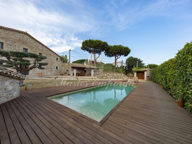 Desde otro ángulo la fachada de la masía y vistas del jardín y piscina