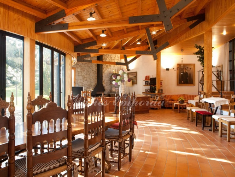 Vista general del gran comedor de la casa de invitados con una gran mesa de madera, el salón con chimenea, con vigas y cubierta de madera