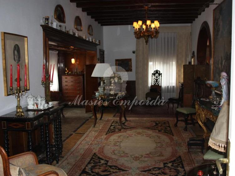 Vista de hall desde el ángulo opuesto a la entrada de la casa con un cuadro de un tamaño extraordinario cubierta con vigas a la vista de madera
