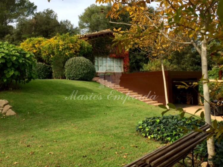 Detalle del jardín y  la casa al fondo de la imagen.