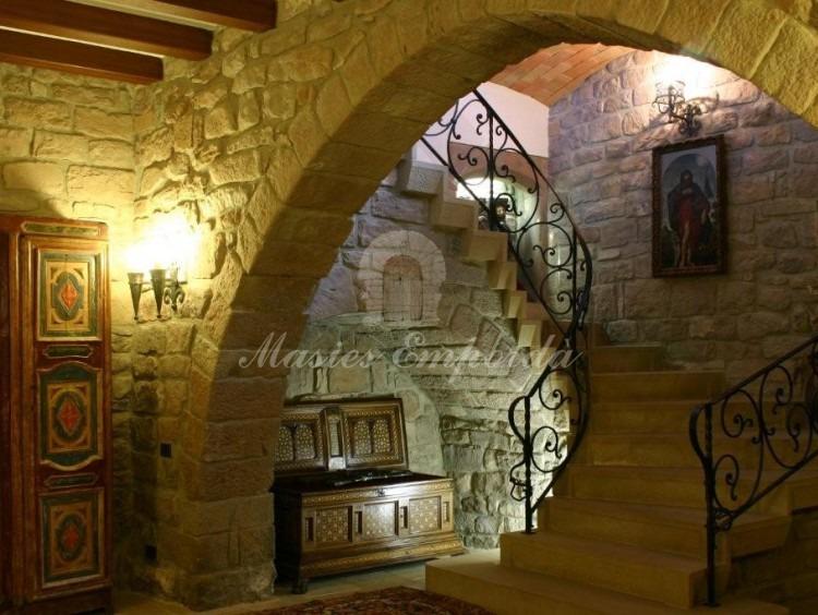 Excepcional escalera en piedra y forja que da acceso a la planta superior de la Masía que esta coronada con un gran arco en piedra