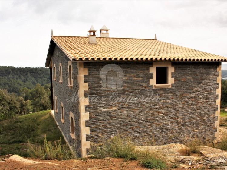 Vista de la masia en el seu conjunt i volum des del lateral de la casa