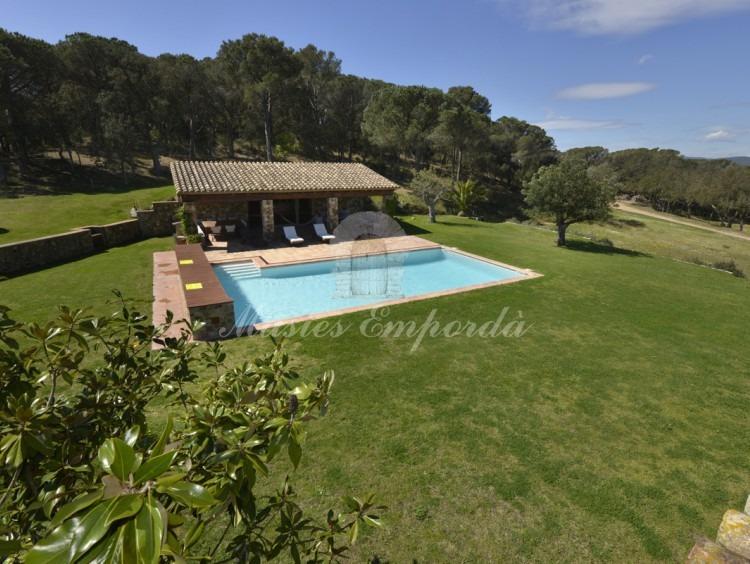 Vista general del jardí i la piscina des de la terrassa de la planta de la masia