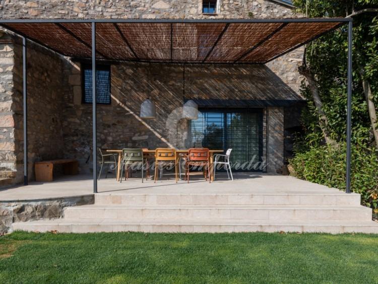 Porxos de la casa amb vista al jardí i la piscina