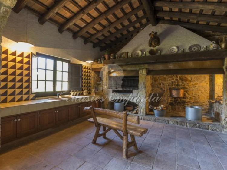 Detalle de la gran cocina con chimenea, rustidos, horno refractario y parrilla barbacoa.