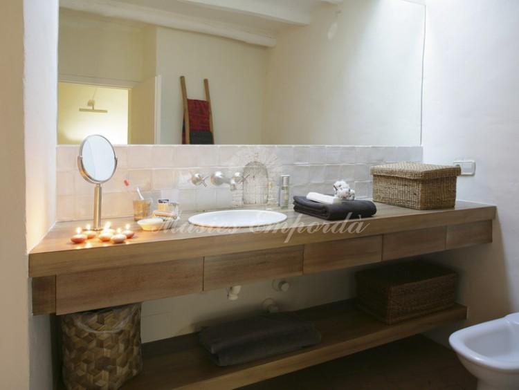 Detalle del baño de la suite con detalles en madera de la encimera del baño con plato de cerámica en blanco